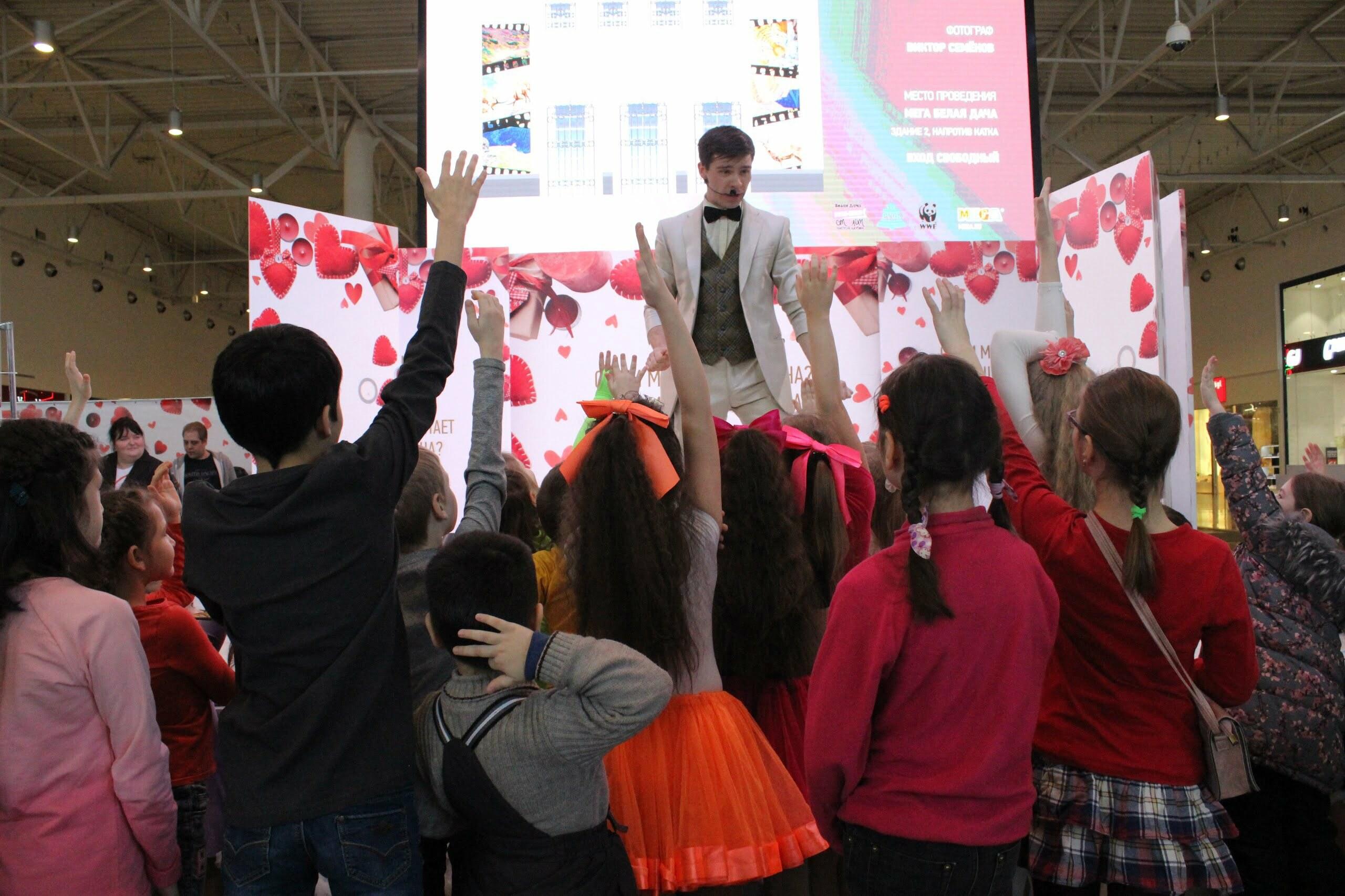 Фокусник в белом костюме на сцене выступает перед детьми