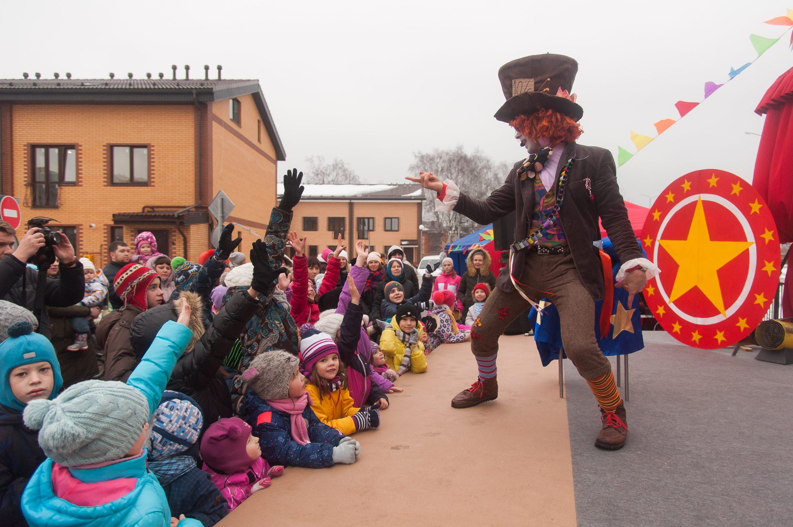 Фокусник Шляпник выступает на сцене перед детьми