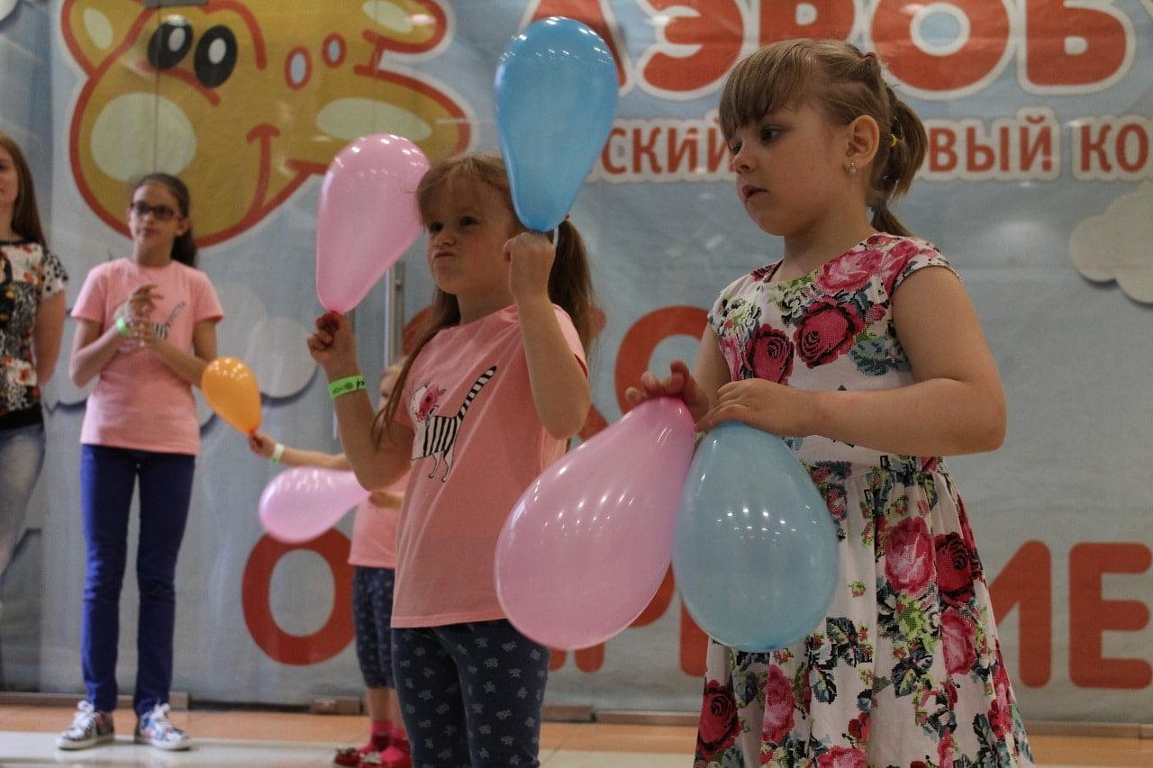 дети стоят на сцене с воздушными шариками