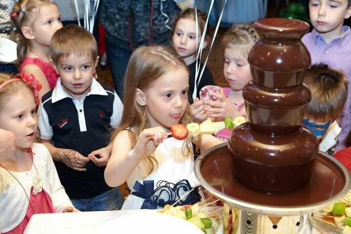 Дети макают фрукты в шоколадный фонтан