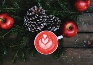 елочная ветка, яблоки и напиток на деревянной поверхности создают рождественскую атмосферу
