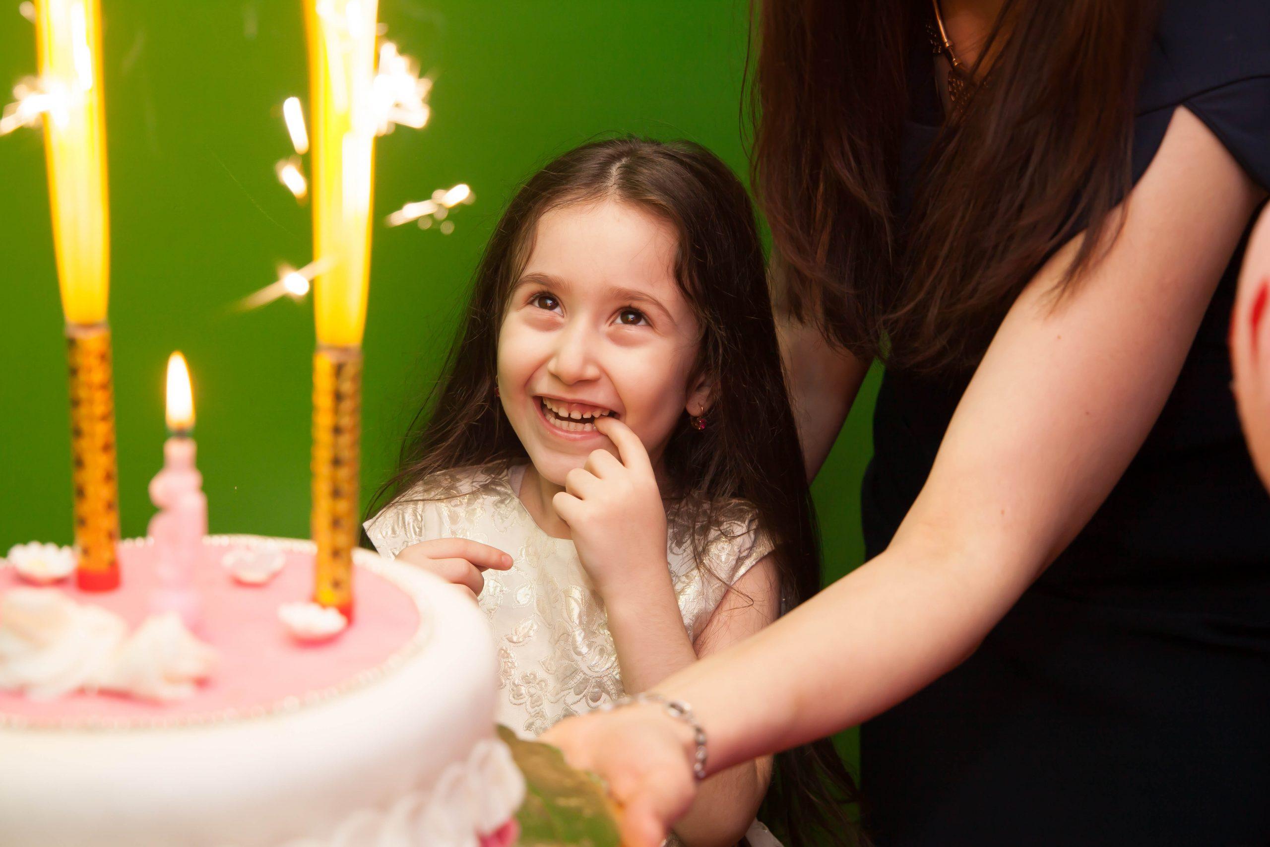 девочка загадывает жеоание перед тем как задуть свечи на торте