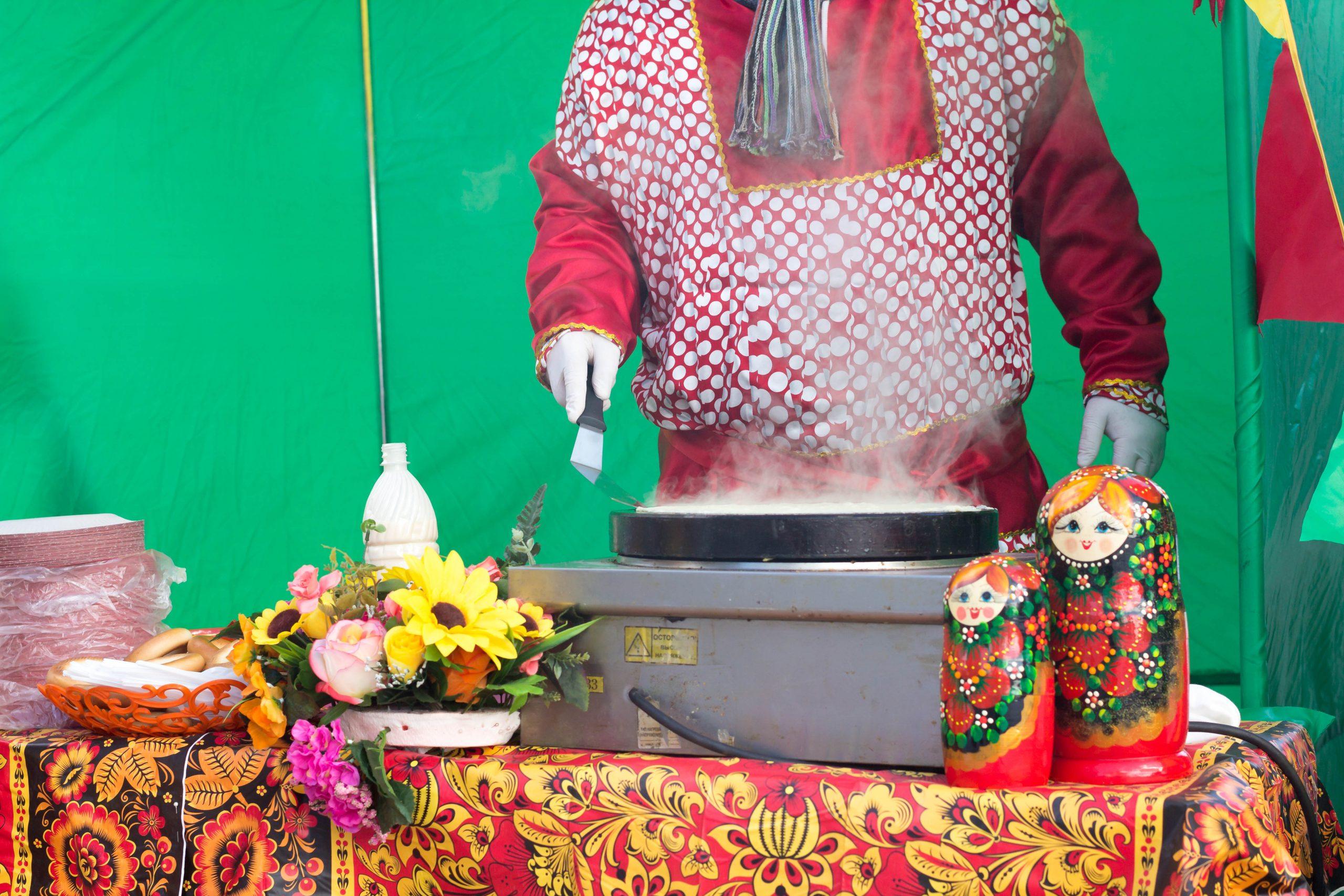 аниматор в русском национальном костюме готовит блины