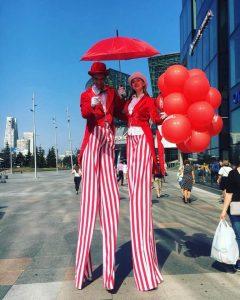 Ходулисты в красно-белых костюмах с воздушными шарами