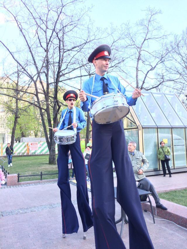 Ходулисты в костюмах полицейских на уличном празднике