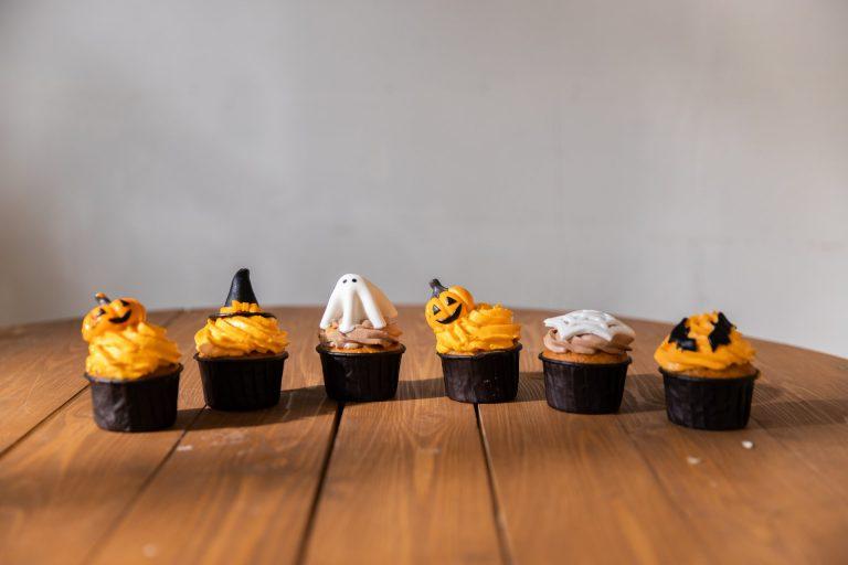 Капкейки в стеле Хэллоуин стоят на деревянном столе