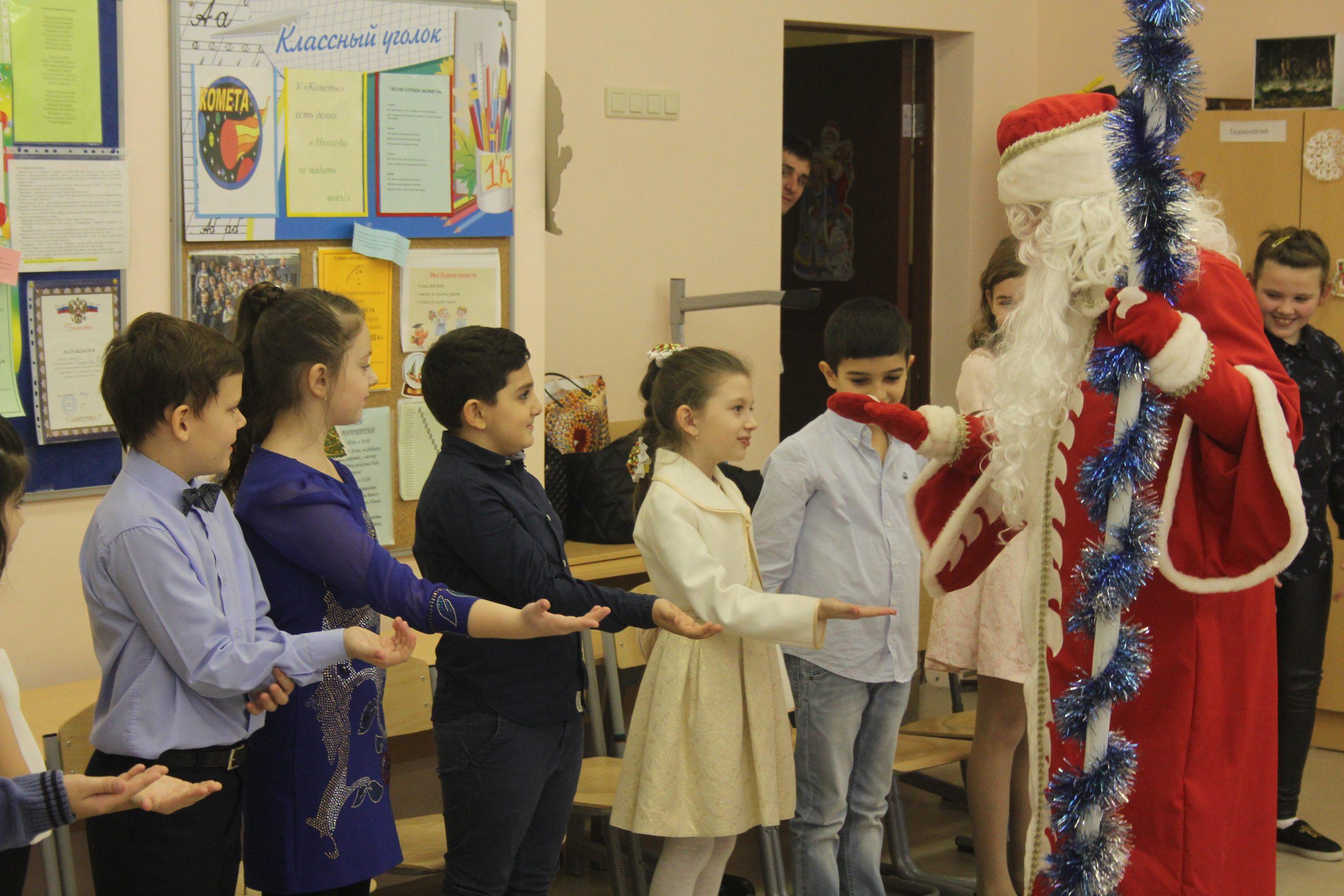 Дед Мороз раздает подарки школьникам в школе