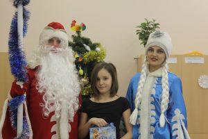 Дед Мороз и Снегурочка фотографируются с ребенком на фоне елки