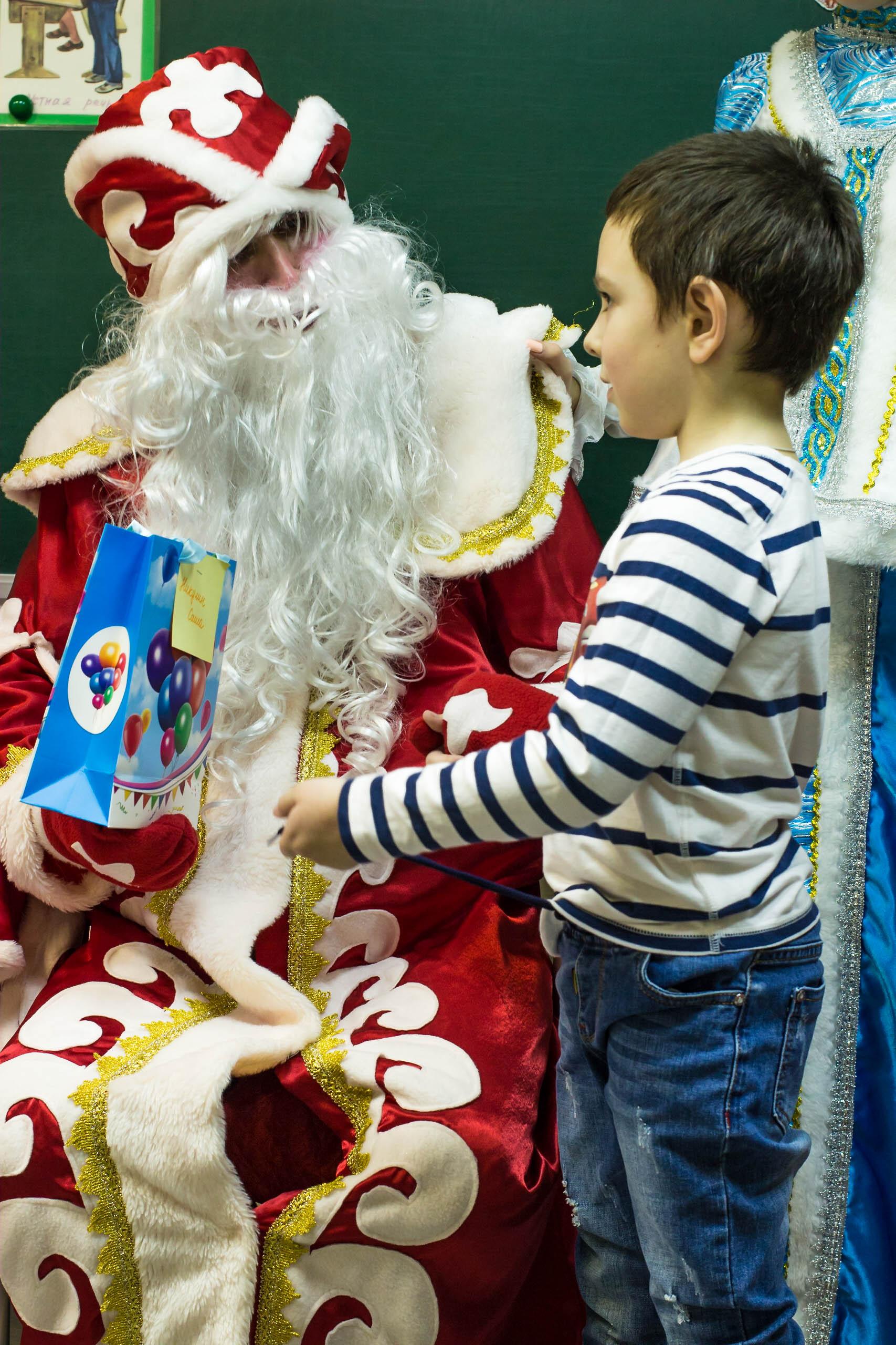 Русский дед Мороз вручает подарок школьнику