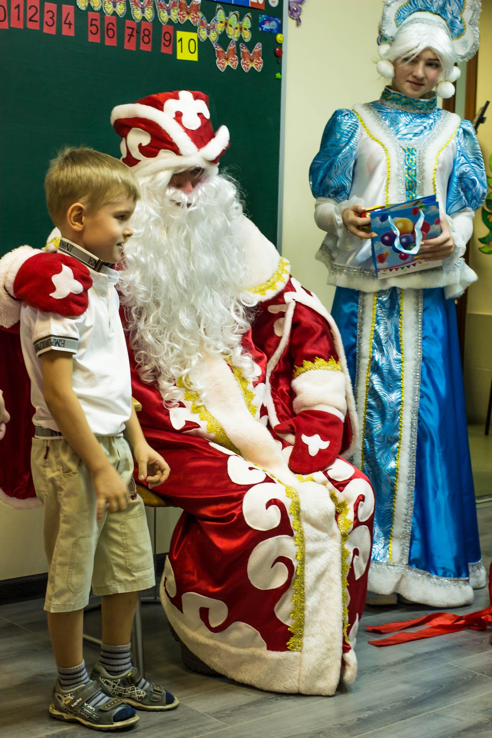 Дед Мороз и Снегурочка дарят ребенку подарок