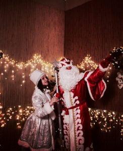 Дед Мороз и Снегурочка на фоне елки и гирлянд