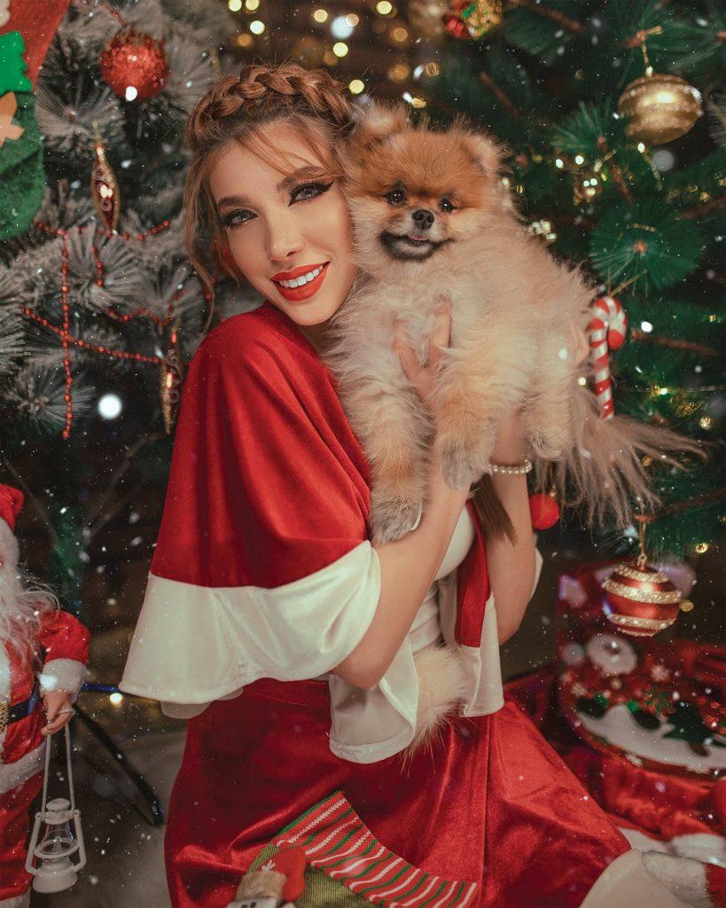 Помощница Санты с собачкой под елкой